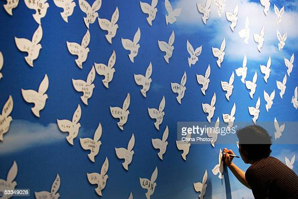 A visitor signs her name on a paper dove during an exhibition on the 1937 Nanjing Massacre at the National Museum August 10 2005 in Beijing China The...