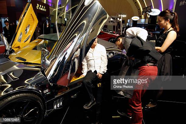 A visitor sits in a Range Rover sports car during the 2010 Top Marques Shanghai at the Shanghai Exhibition Center on October 22 2010 Shanghai China...