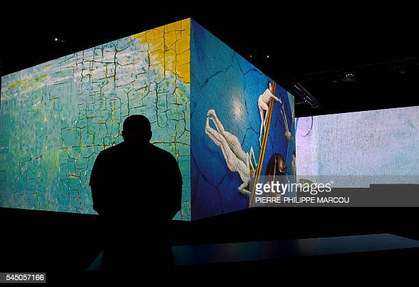 A visitor sits in front of a video installation on Dutch painter Hieronymus Bosch's masterpiece The Garden of Earthly Delights at El Prado museum in...
