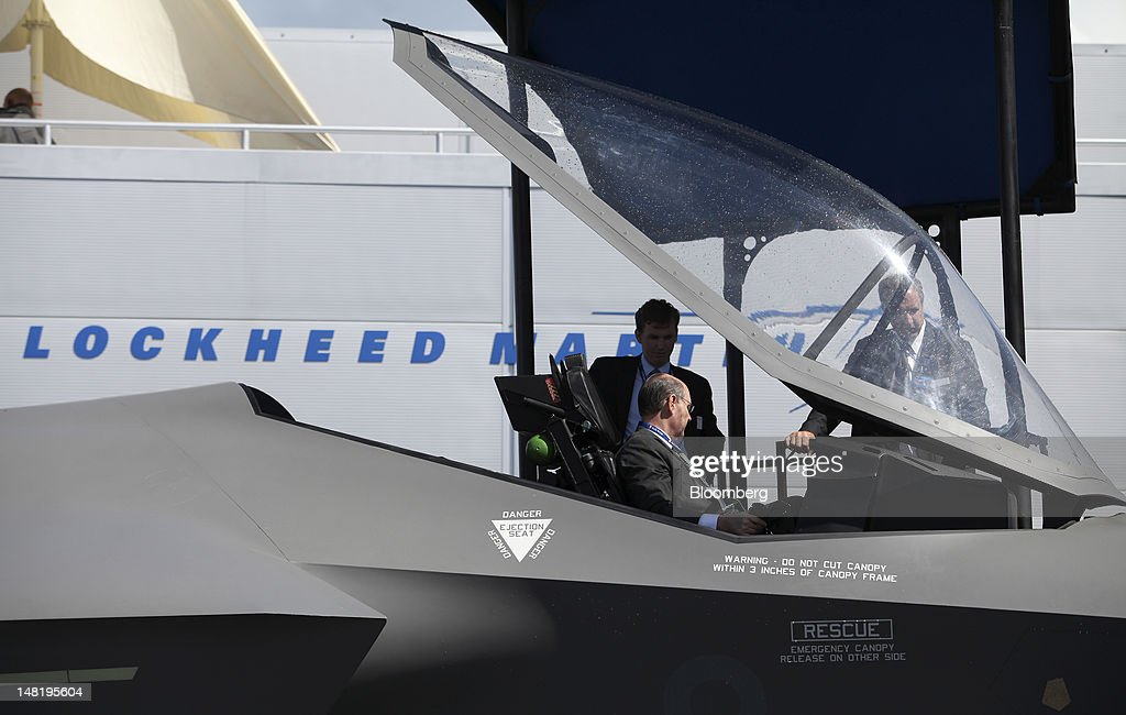 A visitor sits in the cockpit of a Lockheed Martin Corp. F-35 Lightning outside the company's stand on the third day of the Farnborough International Air Show in Farnborough, U.K., on Wednesday, July 11, 2012. The Farnborough International Air Show runs from July 9-15. Photographer: Chris Ratcliffe/Bloomberg via Getty Images