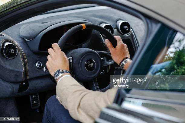 A visitor sits in the driving seat of a McLaren 600LT supercar manufactured by McLaren Automotive Ltd as its launched at the Goodwood Festival of...