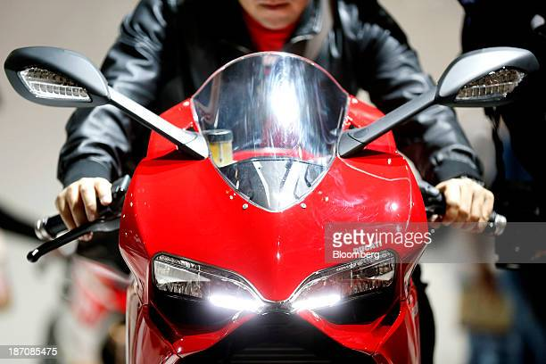 A visitor sits on a Ducati 899 Panigale motorbike produced by Ducati Motor Holding SpA a unit of Audi AG as its stands on display at the...