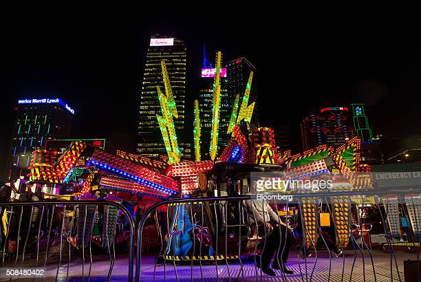 A visitor sits on a fairground ride at the AIA Group Ltd Great European Carnival as the HSBC Holdings Plc headquarters building second right Standard...