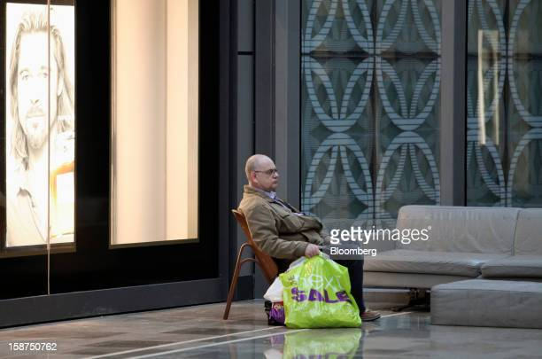 A visitor sits with shopping bags near a poster of US actor Brad Pitt displayed in the window of a Chanel SA perfume store at the Westfield Stratford...