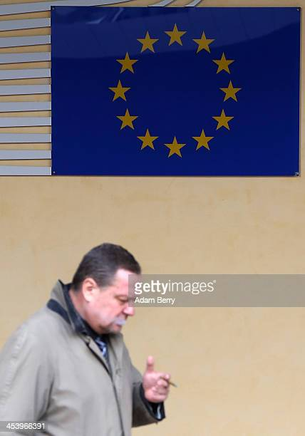 A visitor smokes a cigarette as he passes the Berlaymont building of the European Commission on December 6 2013 in Brussels Belgium The European...