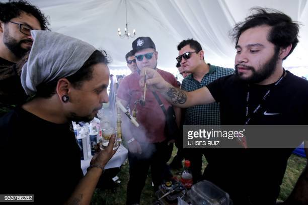 A visitor smokes from a pipe during the first Cannabis Cup where selfcultivation and the quality of the herb are encouraged in Tlajomulco de Zuniga...