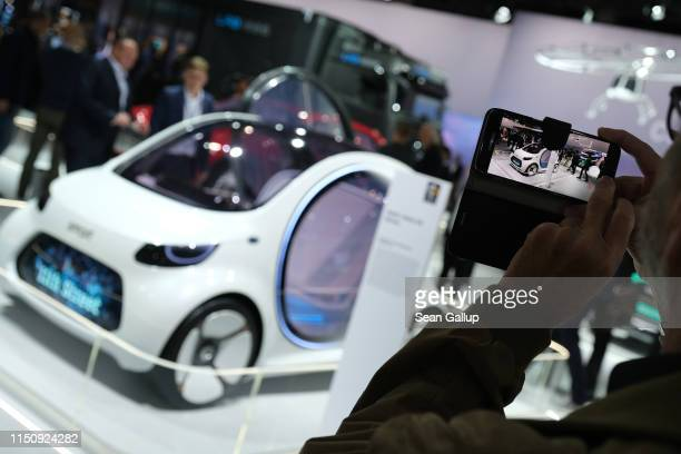 Visitor snaps a photo of a Smart Vision EQ fortwo car on display at the annual Daimler AG shareholders meeting on May 22, 2019 in Berlin, Germany....