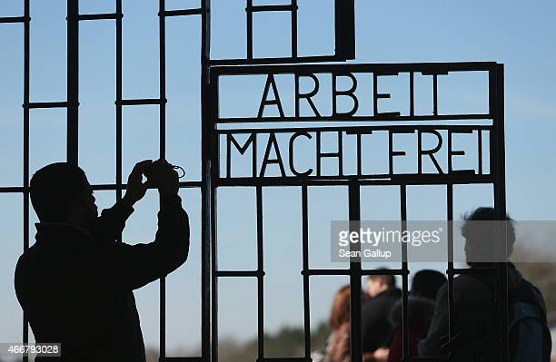 A visitor snaps a photo of the infamous 'Arbeit Macht Frei' inscription at the original entrance gate to the former Sachsenhausen concentration camp...