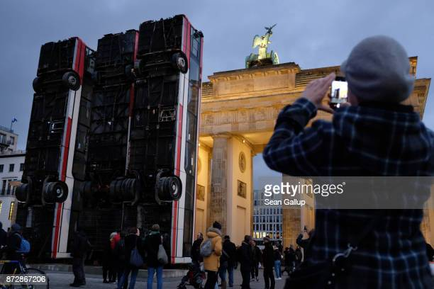 A visitor snaps a photo of three buses standing on end that are an art installation called 'Monument' in front of the Brandenburg Gate on November 11...