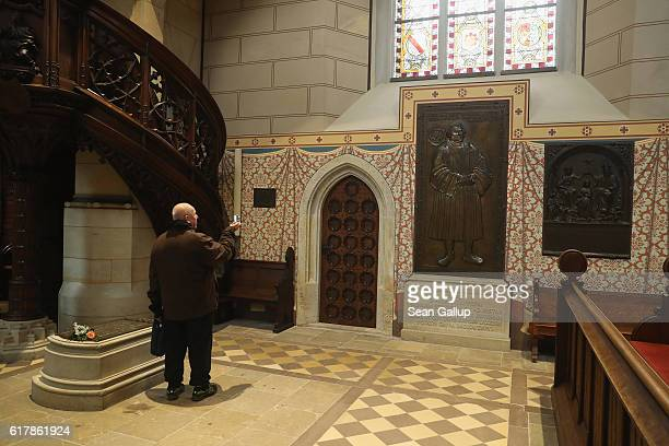 Visitor snaps a photo while standing next to the tomb of Martin Luther in the Schlosskirche church, which is the same church where in 1517 Luther...
