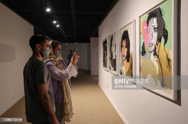 Visitor snaps a picture of late US pop artist Andy Worhol's 1975 prints of Mick Jagger, the lead singer in British rock and roll band The Rolling...