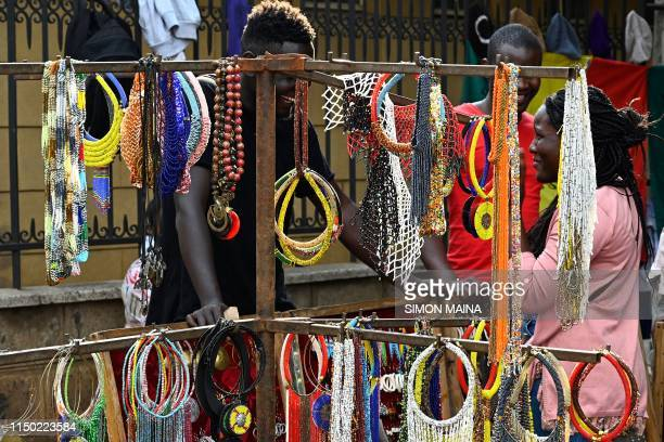 A visitor speaks to a man running a stall selling beaded necklaces displayed at the Maasai market in Nairobi on June 16 2019