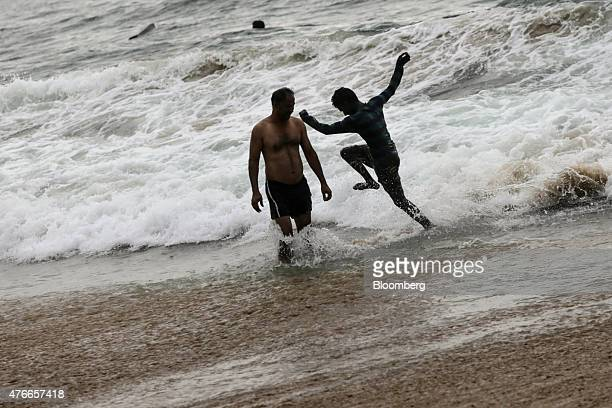 A visitor splashes in the surf at at Kovalam beach in Kovalam Kerala India on Sunday May 31 2015 Prime Minister Narendra Modi is counting on a...