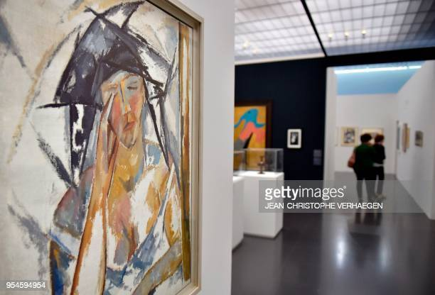 Visitor stand in background of pieces of art by the couple of artists Natalia Gontcharova and Mikhaïl Larionov during the exhibition 'Couples...