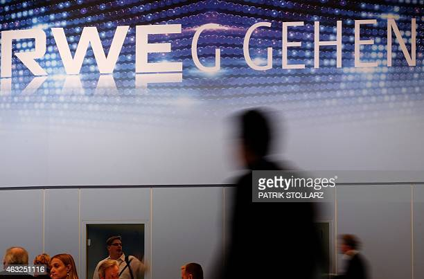 A visitor stand in front of an advertisement of German energy giant RWE at the 'eworld' an energy and water fair on February 12 2015 on the...