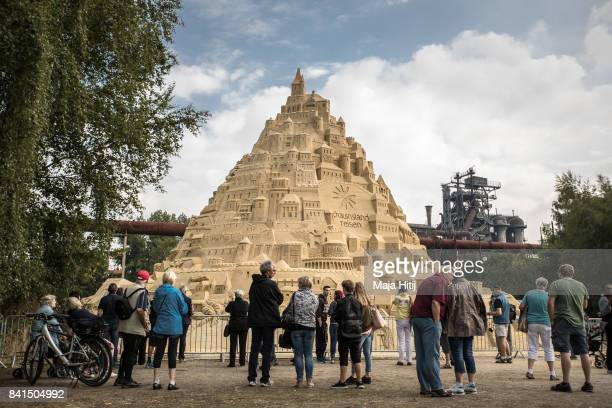Visitor stand near the Sandburg sandcastle on September 1 2017 in Duisburg Germany A local travel agency commissioned the building of the sandcastle...