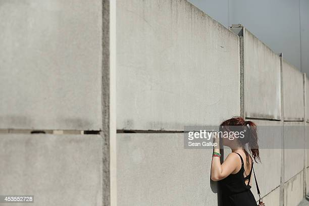A visitor standing on the former east side at the inner structure of the former Berlin Wall peeks between the slits into the former death strip on...
