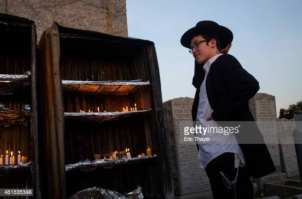 A visitor stands at the gravesite of the Lubavitcher Rebbe Rabbi Menachem Mendel Schneerson June 30 2014 at the Old Montefiore Cemetery in the Queens...
