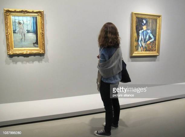 "Visitor stands before the paintings ""Dancer in the artists studio"" of Edgar Degas and ""Lady in Blue"" of Paul Cezanne in the exhibition ""Icons of..."