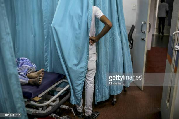 A visitor stands behind a curtain in the emergency ward at a Sudar Hospitals clinic in Chennai India on Thursday July 4 2019 Treating patients will...