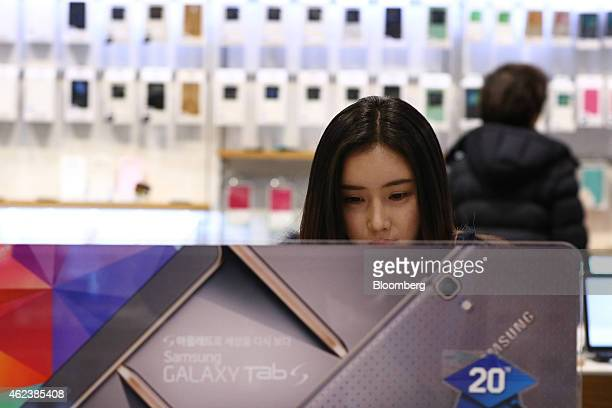 A visitor stands behind an advertisement for the Samsung Electronics Co Galaxy Tab tablet device at the company's d'light flagship store in Seoul...