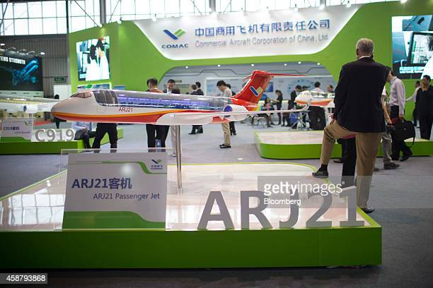 A visitor stands beside a display model of the Commercial Aircraft Corp of China ARJ21 aircraft at the company's stand during the China International...