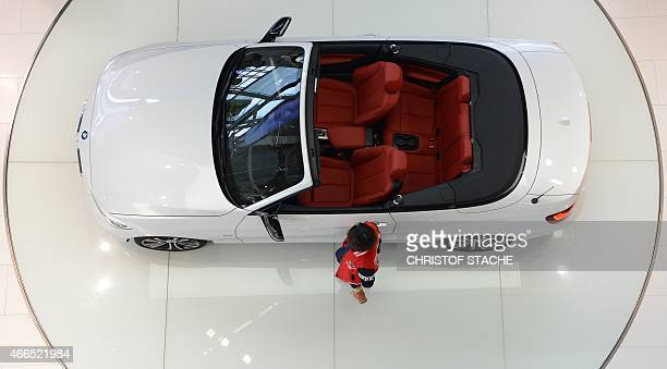 A visitor stands beside a new car of German car maker BMW at the 'BMW World' delivery center near the company's headquarters in Munich southern...