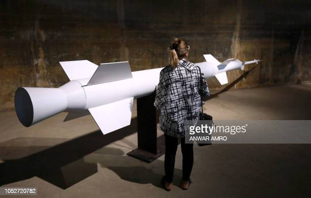A visitor stands by a model rocket during an exhibition commemorating Lebanon's former space programme at the Tripoli International Fair originally...