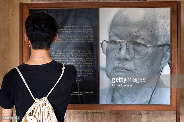 A visitor stands by a photograph of one of the former Khmer Rouge leaders Khieu Samphan in one of the rooms of Tuol Sleng prison also known as S21 on...
