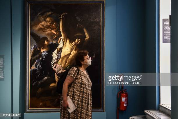 """Visitor stands by """"St. Sebastian tended by Angels"""" , a 1660-70 oil on canvas by Italian painter Giacinto Brandi, during the exhibition """"Caravaggio's..."""