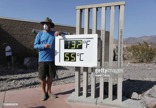 Visitor stands for a photo in front of an unofficial thermometer at Furnace Creek Visitor Center on August 17, 2020 in Death Valley National Park,...