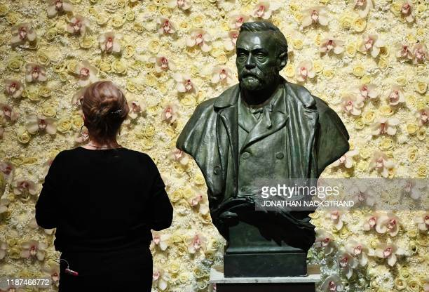 TOPSHOT A visitor stands in front of a bust of the Nobel Prize founder Alfred Nobel prior the Nobel awards ceremony at the Concert Hall in Stockholm...