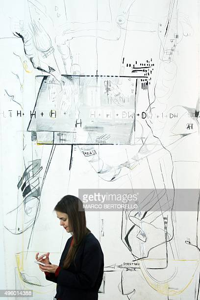 A visitor stands in front of a painting by German artist Anne Imhof during the 'Artissima' art fair at Oval Lingotto on November 6 2015 in Turin The...