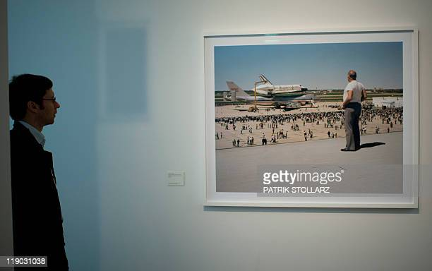 """Visitor stands in front of the photo """"The space shuttle Colombia lands on Air Force Base Kelly Lackland San Atonio 1979"""" from American photographer..."""