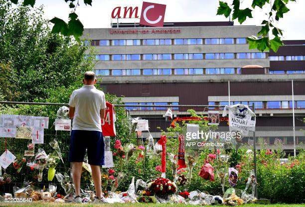 A Visitor stands in silence next to items placed next to the hospital where the Ajax midfielder Abdelhak Nouri receives treatments in Amsterdam on...
