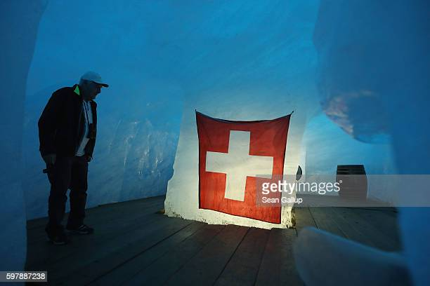 A visitor stands inside an icecavern room with a Swiss flag that lies at the end of a 100meterlong tunnel hewn into the Rhone glacier as a tourist...