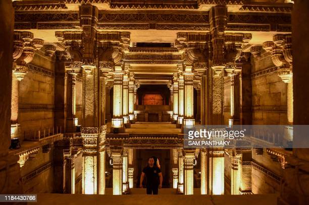 Visitor stands inside the Adalaj-Ni-Vav ancient stepwell illuminated on the occasion of the 'Water Festival' organised by Craft of Art, an initiative...