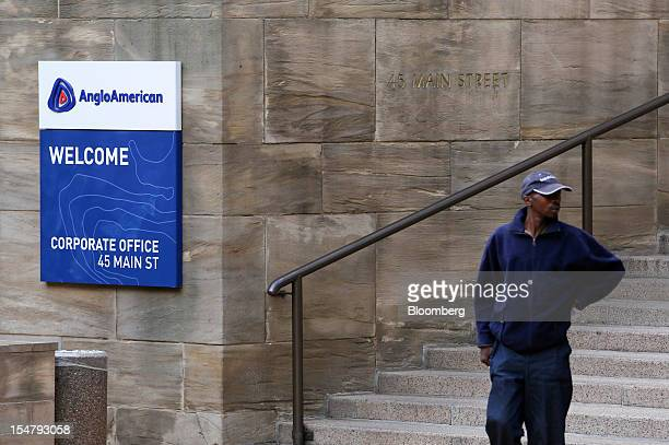 A visitor stands near a company sign outside the offices of Anglo American Plc in the Marshalltown district of Johannesburg South Africa on Friday...