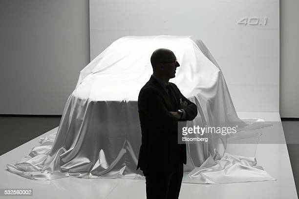 A visitor stands near a covered Volvo 401 concept automobile ahead of its unveiling at a media event at the headquarters of Volvo Car Group in...