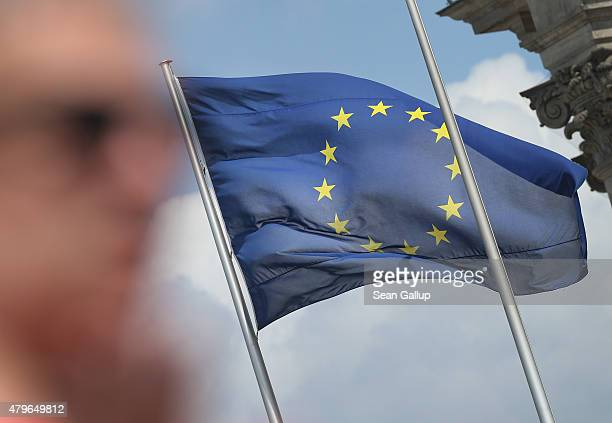 A visitor stands near a flag of the European Union at the Reichstag the day after a majority of people voted 'no' in the Greek referendum on July 6...