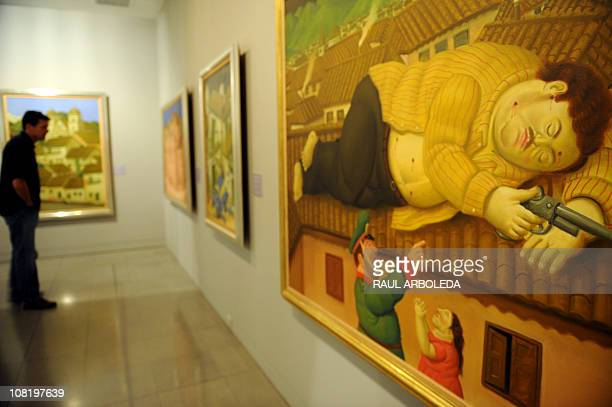 A visitor stands near a painting named Dead Pablo Escobar by Colombian Artist Fernando Botero displayed at the Antioquia Museum in Medellin Antioquia...