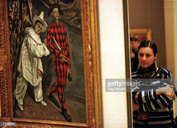"""Visitor stands near Paul Cezanne's """"Mardi Gras or Pierrot and Harleqin"""" during the opening of the exibition called """"Cezanne and Russian Avant-Garde""""..."""