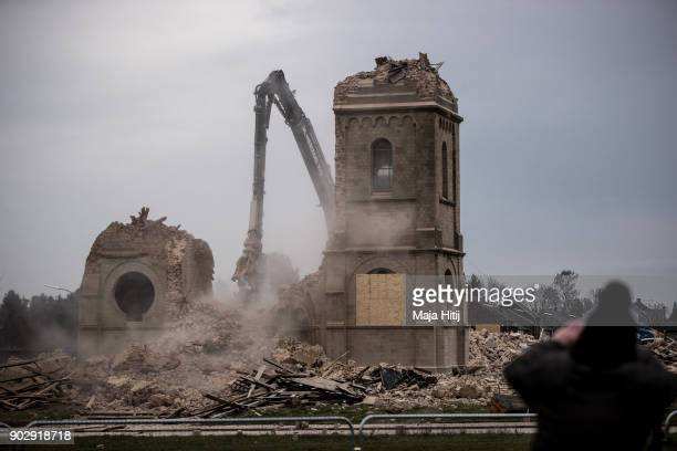Visitor stands nearby as an excavator demolishes Saint Lambertus church following protests by activists on January 9 2018 in Immerath Germany The...