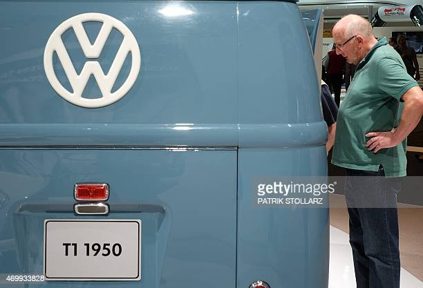 A visitor stands next to a VW T1 vintage bus from the year 1950 at the 'Techno Classica' fair in the western German city of Essen on April 16 2015...