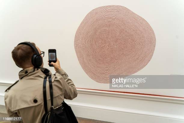A visitor stands next to an art installation entitled 'Exercise Between Blood and Earth' during a presspreview at The Royal Academy of Arts in London...