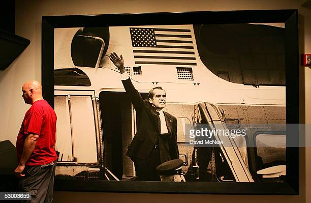 A visitor stands next to an image of President Richard Nixon waving near the Watergate Era portion of the Nixon museum at the Richard Nixon Library...