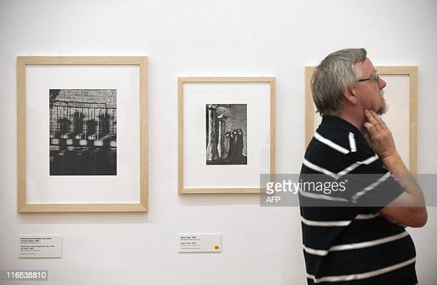 A visitor stands next to Hungarianborn US photographer Andre Kertesz' 'Chimney Stack Shadows on a Fire Escape 1961' at the Kertesz retrospective at...