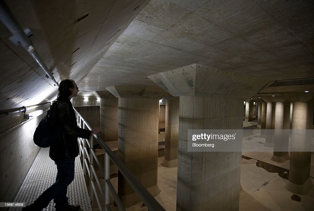 A visitor stands on a platform in the surge tank area of the Metropolitan Area Outer Underground Discharge Channel in Kasukabe City, Saitama Prefecture, Japan, on Wednesday, Nov. 21, 2012. The facility called 'Underground Temple' was constructed to protect the capital Tokyo against flooding and is one of the largest underground water diversion facilities in the world. Photographer: Tomohiro Ohsumi/Bloomberg via Getty Images