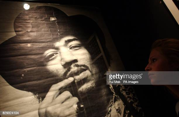 A visitor studies a poster on display at the press preview for the exhibition Jimi At The Marquee featuring the world's largest collection of Jimi...