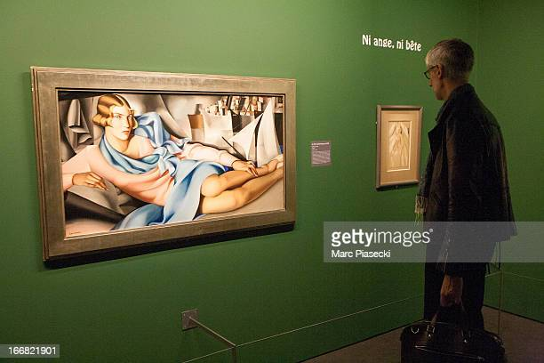 A visitor studies an exhibit on display at the Exhibition 'Tamara de Lempicka Queen of the Art Deco' exhibition opening at La Pinacotheque on April...